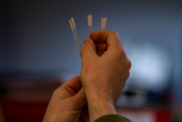 An Airman holds up six Nasopharyngeal swabs.