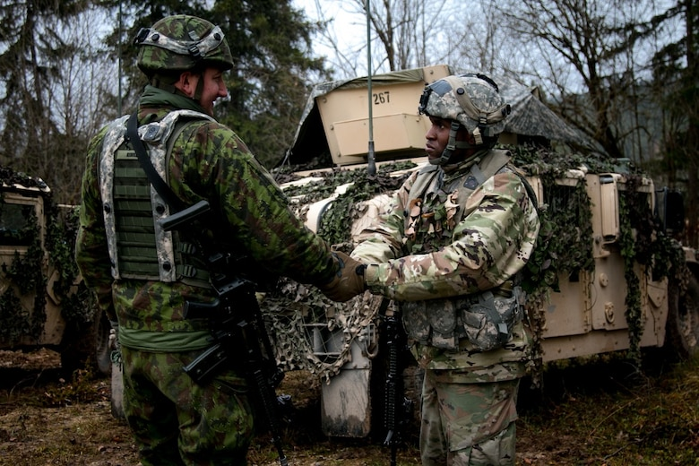 Sgt Azeez Bilaali (right), a psychological operations specialist assigned to 351st Tactical Psychological Operations Company in Fort Totten, N.Y., shakes hands with Sgt. Rimas Rimkus, a soldier in the Lithuanian armed forces, after a mission brief during the Allied Spirit VII training evercise in Grafenwoehr, Germany on Nov. 17, 2017. The U.S. Army, along with its allies and partners, continues to forge a dynamic presence with a powerful land network that simultaneously deters aggression and assures the security of the region. Approximately 3,700 service members from 13 nations gathered in 7th Army Training Command's Hohenfels Training Area in southeastern Germany to participate in the seventh iteration of Allied Spirit, which is scheduled from Oct. 30 - Nov. 22, 2017. (U.S. Army photo by Spc. Dustin D. Biven / 22nd Mobile Public Affairs Detachment)