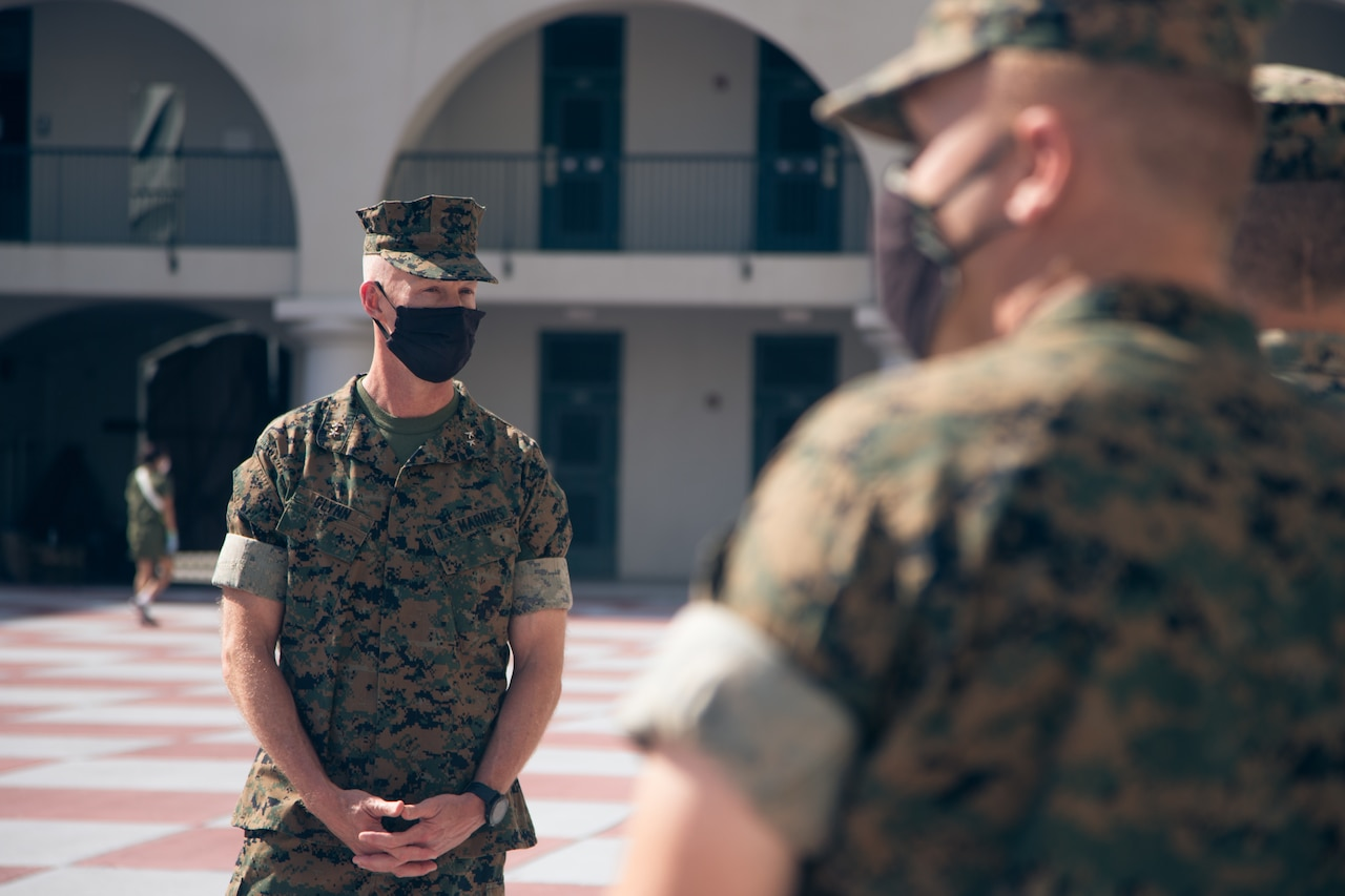 Marine Corps officer wearing a face mask speaks with young Marines.