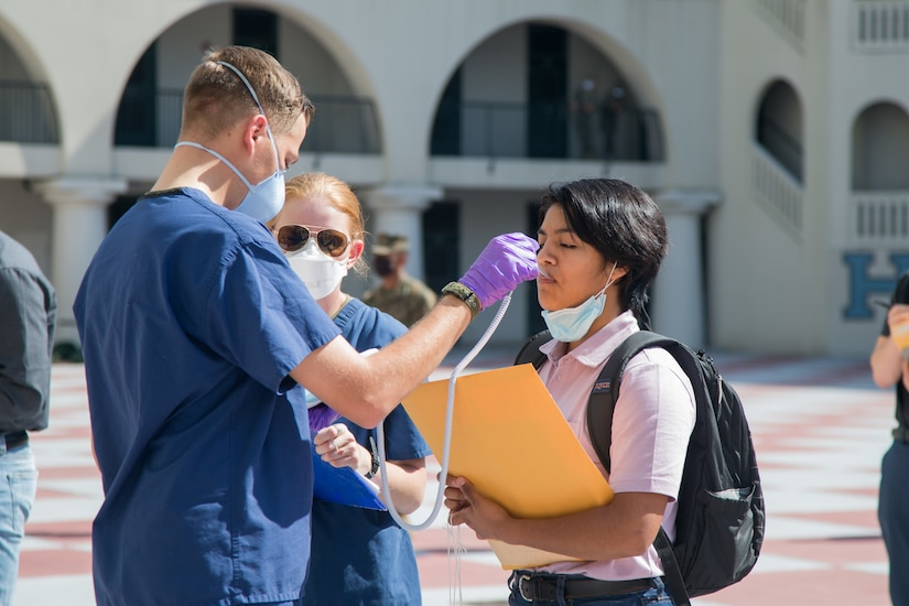 Marines wearing blue scrubs and face masks take the temperature of a new enlisted woman, who is dressed in civilian clothes.