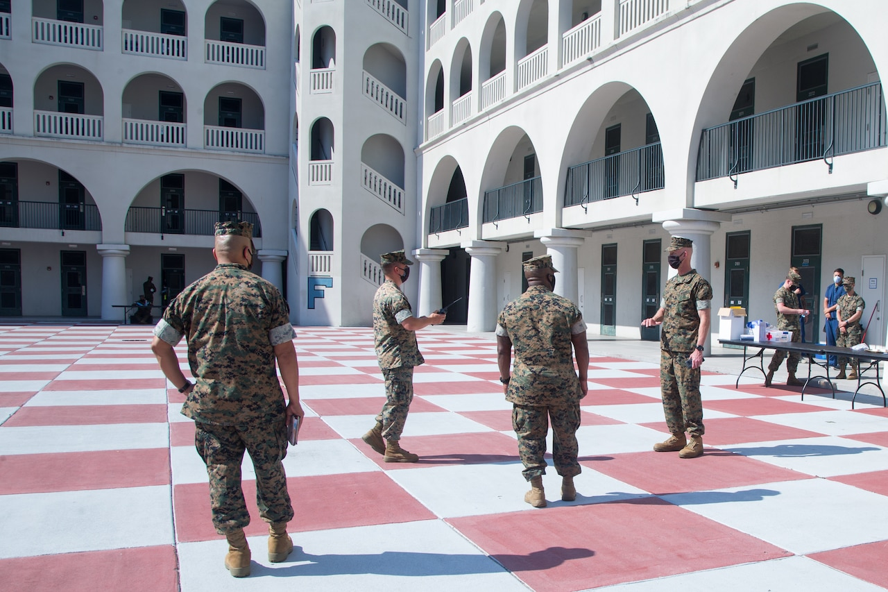 Marines wearing masks stand in a dormitory courtyard.