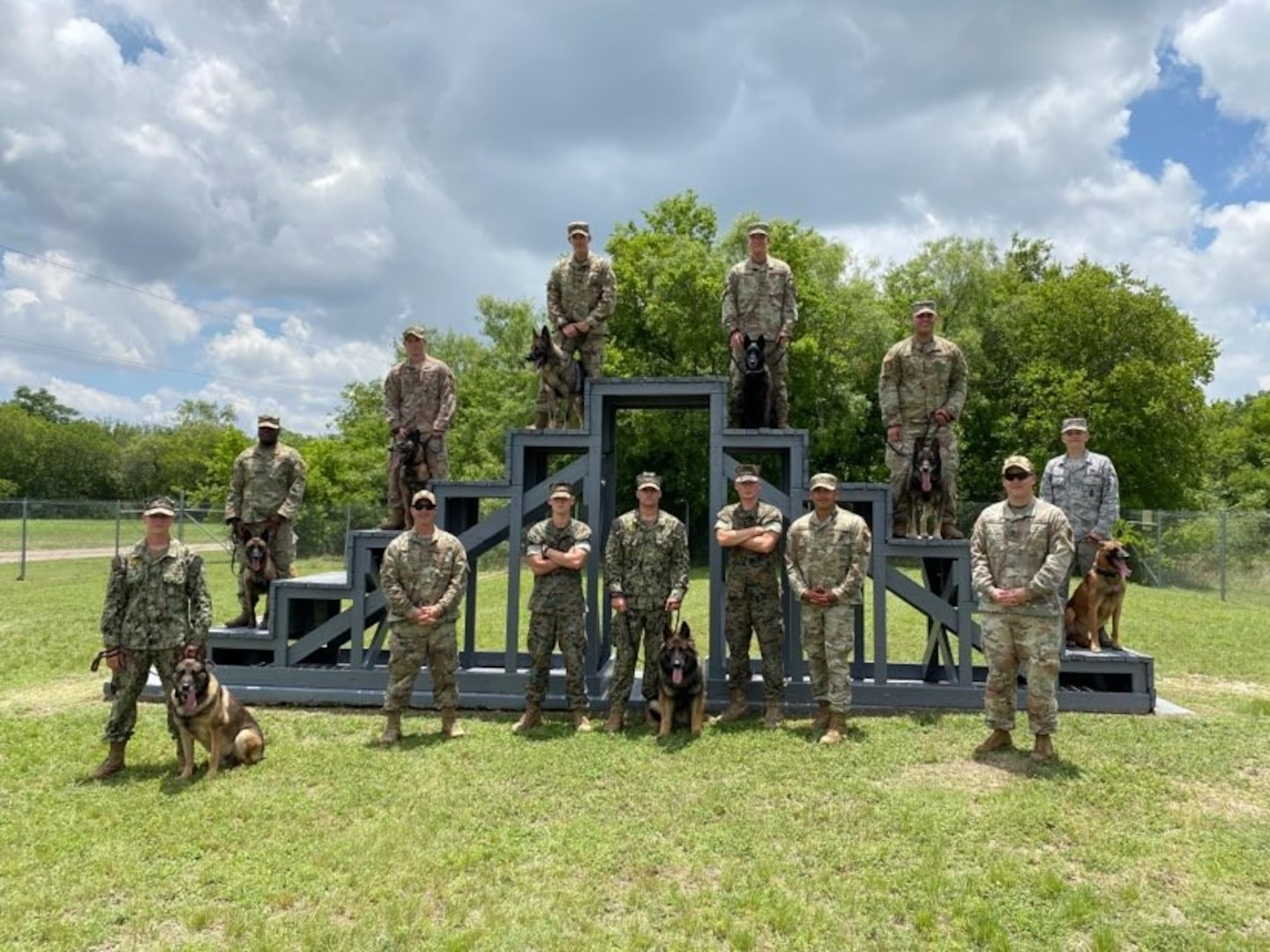 Military working dog handler training students from the Army, Air Force, Marine Corps and Navy pose for a photo following a K-9 demonstration for the Fair Oaks, Texas, Rotary Club June 3, 2020, at Joint Base San Antonio-Lackland.