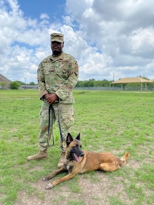 A military working dog handler who trains students from the Air Force poses for a photo following participation in a K-9 demonstration for the Fair Oaks, Texas, Rotary Club June 3, 2020, at Joint Base San Antonio-Lackland.