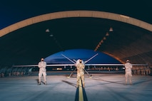 Three Airmen from the 432nd Aircraft Maintenance Squadron stand in front of an MQ-9 Reaper at night.