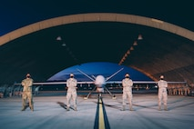 Four Airmen from the 432nd Aircraft Maintenance Squadron, Tiger Flight, stand in front of an MQ-9 Reaper at night.