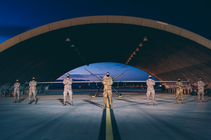 Airmen in protective masks, due to COVID-19, pose for a photo in front of an MQ-9 Reaper at night.