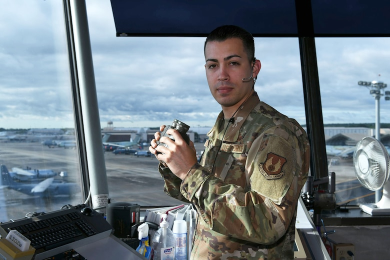 Photo shows an Airman standing inside the air control tower holding binoculars in his hands.