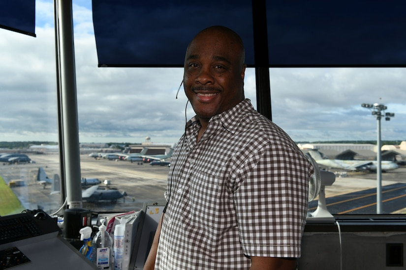 Photo shows a man smiling at the camera from inside the air traffic control tower.