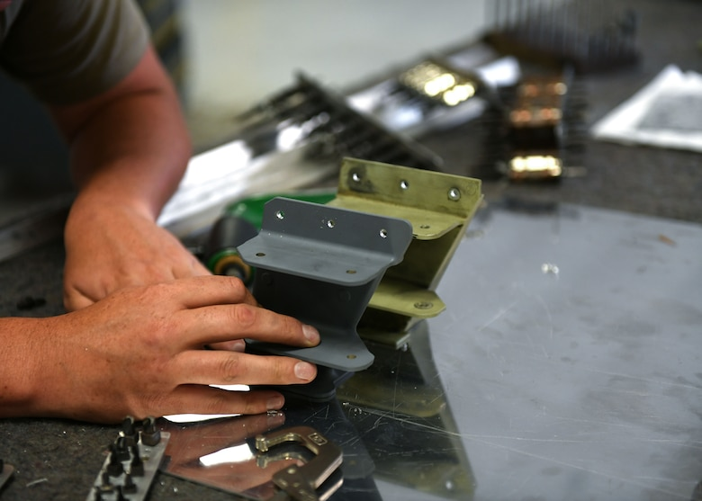 Tech. Sgt. Jason Felts, 19th Maintenance Squadron sheet metal production lead, compares an old hydraulic pump bracket to the new 3D printed version at Little Rock Air Force Base, Arkansas, June 4, 2020. The re-creation of the part acted as an opportunity to completely revamp the structure and strength of the part to decrease the amount of repairs that are needed over time. (U.S. Air Force photo by Airman 1st Class Jayden Ford)