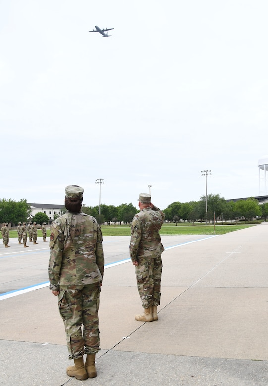 U.S. Air Force Col. Heather Blackwell, 81st Training Wing commander, and Chief Master Sgt. David Pizzuto, 81st TRW command chief, watch a C-130J Hercules conduct a fly-over in honor of Pizzuto's retirement on the Levitow Training Support Facility drill pad at Keesler Air Force Base, Mississippi, May 15, 2020. Pizzuto retires with 37 years of military service. (U.S. Air Force photo by Kemberly Groue)