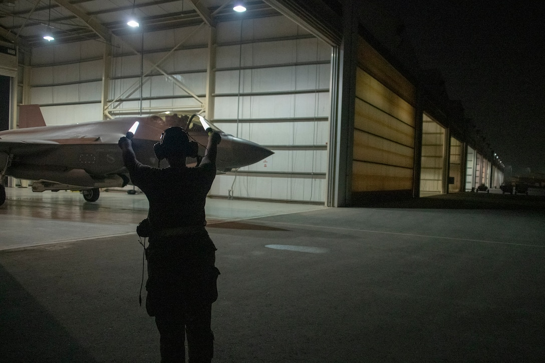 U.S. Air Force Capt. Emily Thompson, 421st Expeditionary Fighter Squadron pilot, launches an F-35A Lightning II while Airman 1st Class Ashlin Randolph, a 380th Aircraft Maintenance Squadron weapons load crew member, gives the signal to proceed on the Al Dhafra Air Base, United Arab Emirates, flightline June 5, 2020.Thompson is the first female to fly an F-35A Lightning II into combat. She was also launched by an all-female maintenance crew.  (U.S. Air Force photo by Tech. Sgt. Kat Justen)