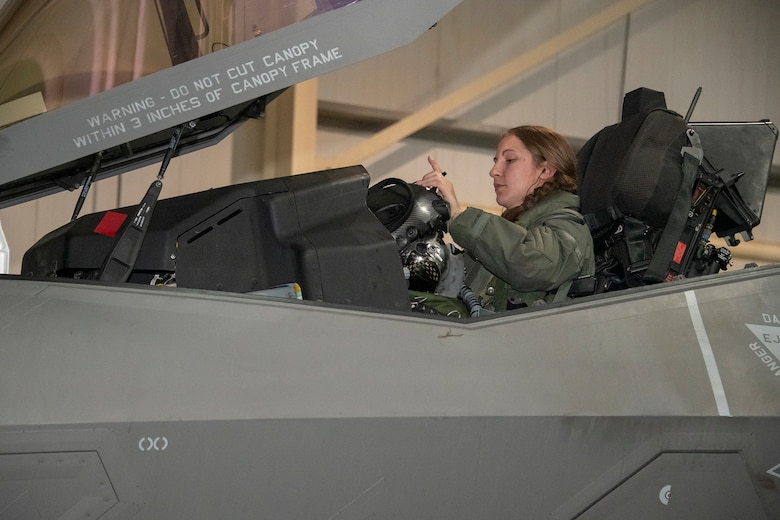 U.S. Air Force Capt. Emily Thompson, 421st Expeditionary Fighter Squadron pilot, dons her helmet prior to a mission at Al Dhafra Air Base, United Arab Emirates, June 5, 2020. Thompson is the first female to fly an F-35A Lightning II into combat. She is currently deployed from Hill Air Force Base, Utah. (U.S. Air Force photo by Tech. Sgt. Kat Justen)