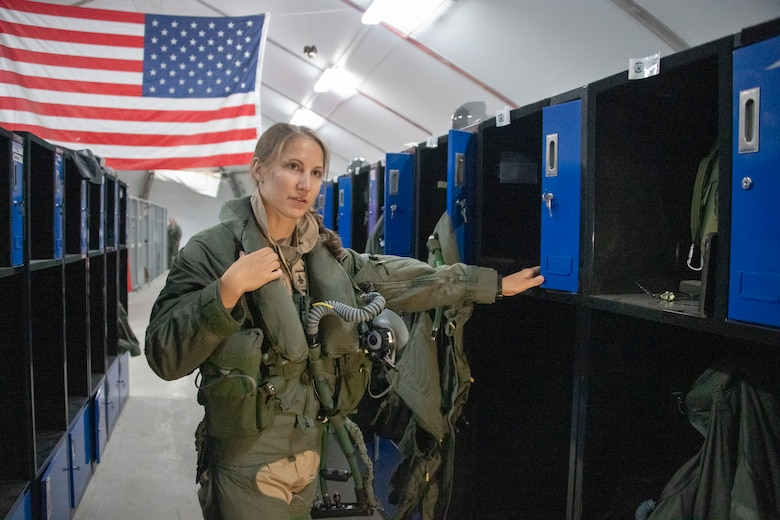 U.S. Air Force Capt. Emily Thompson, 421st Expeditionary Fighter Squadron pilot, dons flight equipment at the Aircrew Flight Equipment shop on Al Dhafra Air Base, United Arab Emirates, June 5, 2020. Thompson is the first female to fly an F-35A Lightning II into combat. She is currently deployed from Hill Air Force Base, Utah. (U.S. Air Force photo by Tech. Sgt. Kat Justen)