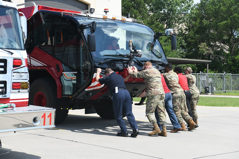 Photo shows group of six people pushing a fire truck backwards into its hangar while a person inside the truck is reversing it.