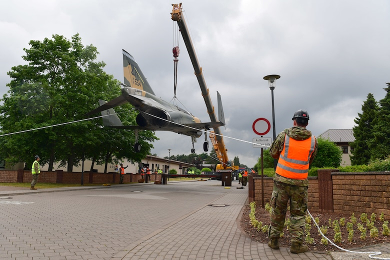 Workers hold a jet aircraft being lifted by a crane steady with ropes.