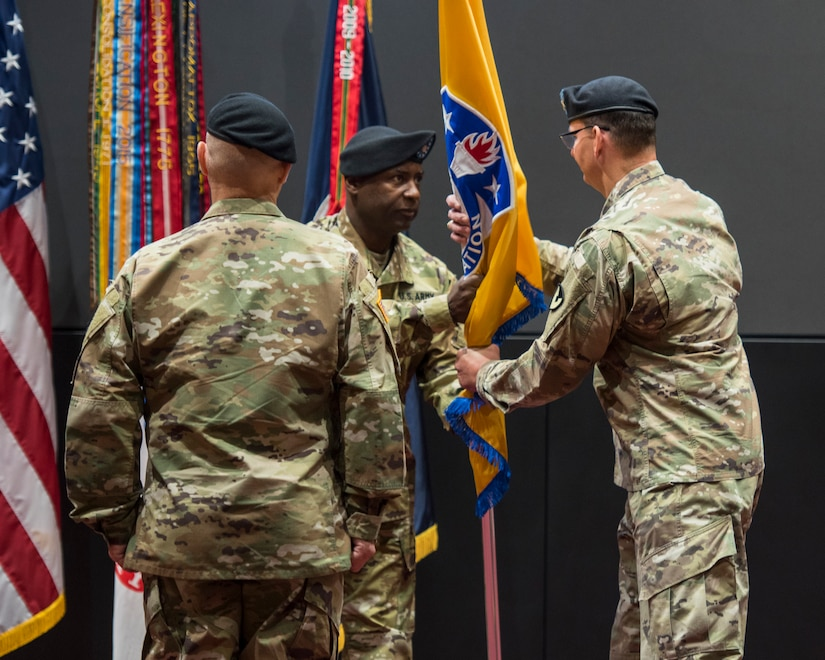 Command Sgt. Maj. Gene Canada, U.S. Army Security Assistance Command's command sergeant major, passes the colors to Maj. Gen. Jeffrey Drushal, outgoing commander, during a relinquishment of command ceremony, 2 June 2020, at Redstone Arsenal, AL.