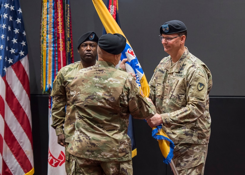 Maj. Gen. Jeffrey Drushal, U.S. Army Security Assistance Command's commanding general, the outgoing commander, passes the colors to Lt. Gen. Edward Daly, deputy commanding general of Army Materiel Command, while Command Sergeant Major Gene Canada, center, observes.