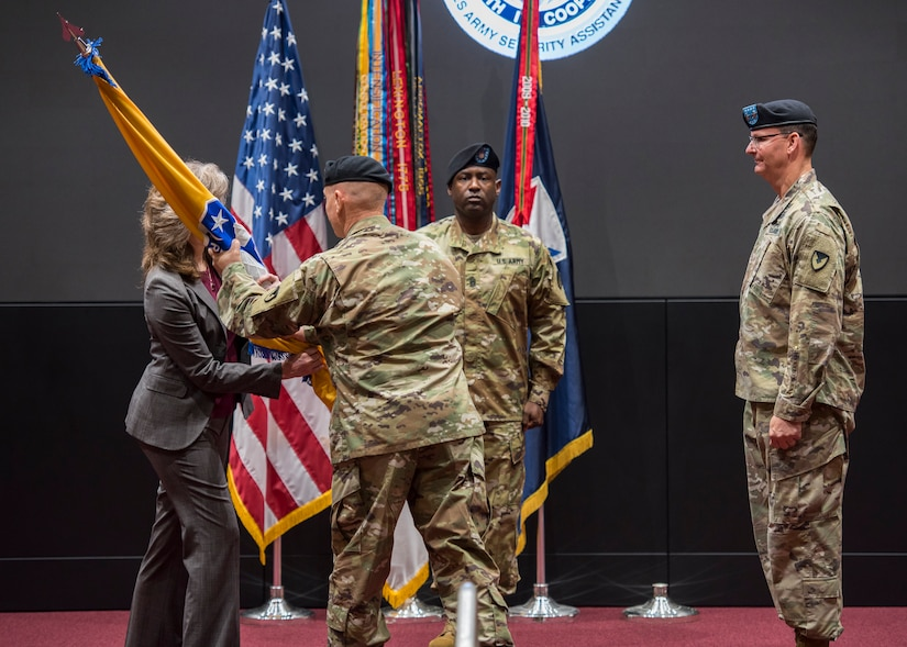 Lt. Gen. Edward Daly, deputy commanding general of Army Materiel Command, passes the colors to Dr. Myra  Gray, U.S. Army Security Assistance Command's Senior Executive Service officer and deputy to the commanding general, who will assume Executive Director duties upon the conclusion of the relinquishment of command ceremony, 2 June 2020, at Redstone Arsenal.