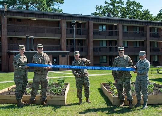 Col. Brian Montgomery, 4th Fighter Wing vice commander, center, and members of Team Seymour cut the ribbon at the opening of the Dorm Community Garden at Seymour Johnson Air Force Base, North Carolina, June 8, 2020.