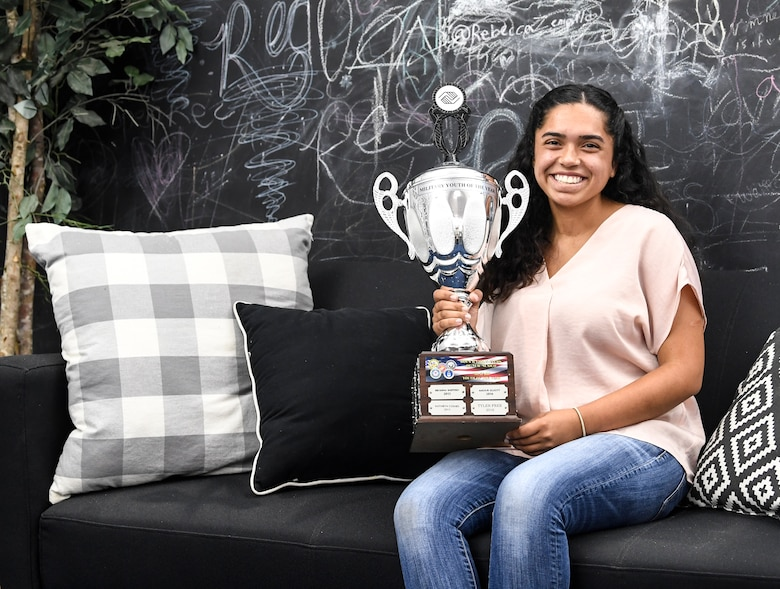 A girl holds her trophy.