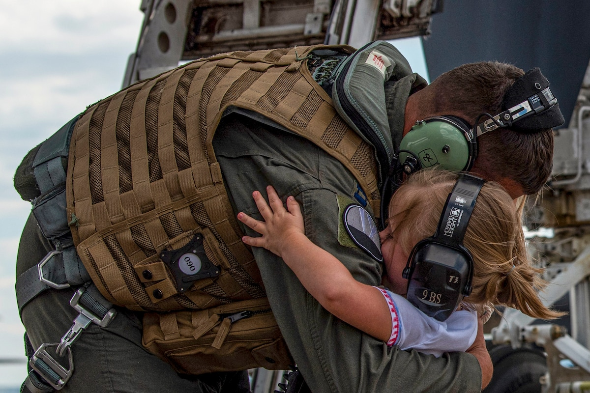 An airman wearing headphones hugs a young girl on a flightline, who is also wearing headphones.