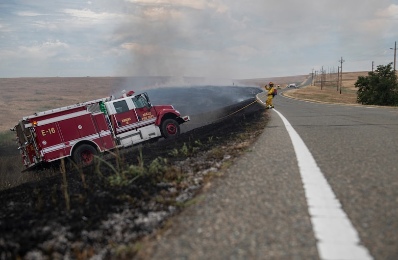 A 9th Civil Engineer Squadron firefighter directs the driver up a slope on Beale Air Force Base.