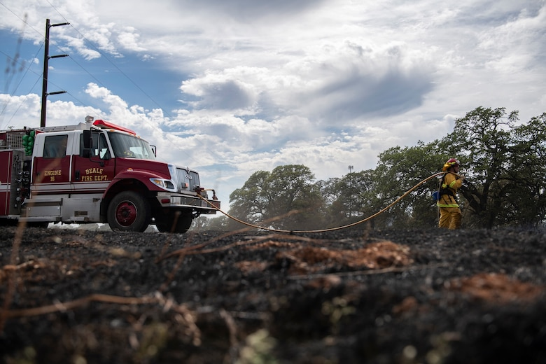 9th Civil Engineer Squadron firefighters extinguish hot spots of a wildfire on Beale Air Force Base.