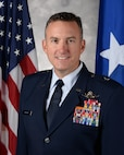 An U.S. Air Force general officer stands for an official photo in front of the American flag and general officer flag.