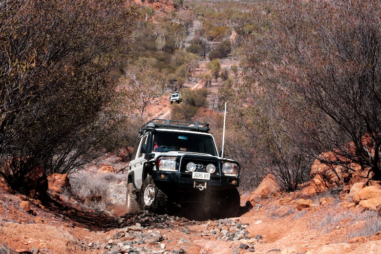 Airmen assigned to the 709th Technical Maintenance Squadron, Detachment 421, drive to a maintenance site in the outback of Alice Springs, Australia, Aug. 28, 2019. The Airmen receive special driving training once assigned to deal with the rough terrain and road hazards, which include kangaroos and free-roaming camels. (U.S. Air Force photo illustration by Master Sgt. Benjamin Wilson)