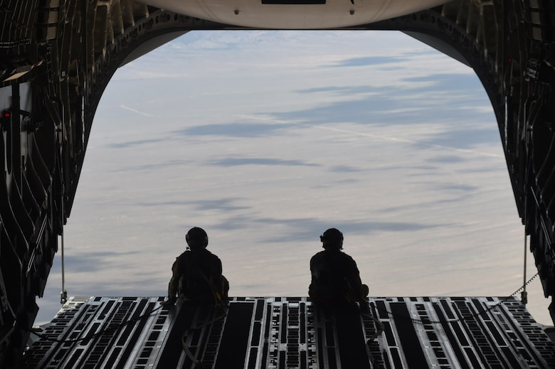 Master Sgt. Anthony Leonard and Staff Sgt. Jason Conner, 7th Airlift Squadron loadmasters, sit on the end of an open cargo bay of a C-17 Globemaster III over the Nevada Test and Training Range, Nev., June 6, 2020. As part of a joint force exercise designed to improve readiness, ten C-17s conducted a simulated air drop mission over the Nevada Test and Training Range. (U.S. Air Force photo by Airman 1st Class Mikayla Heineck)