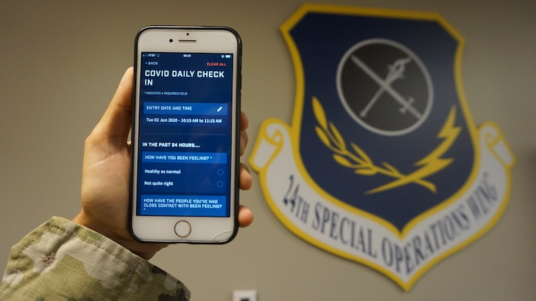 An Airman assigned to the 24th Special Operations Wing, holds up a smartphone with a dark blue unit shield reading 24th special operations wing in the background.