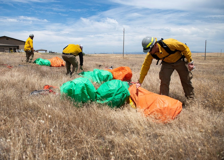Instructors check how well 9th Civil Engineer Squadron firefighters deployed into their fire shelters.