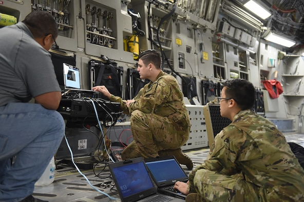 From left to right, Joseph Labosa, Department of Defense contractor, Staff Sgt. Mehmet Yasdiman, 1st Airlift Squadron communications systems operator, and Staff Sgt. Richie Sounantha, Air Mobility Command cyber transport systems technician, test a fixed installation satellite antenna (FISA) connection onboard a C-17 Globemaster III on Joint Base Lewis-McChord, Wash., June 5, 2020. The FISA was set up to work with a dynamic re-tasking capability (DRC) system, enabling higher connection speeds and more efficient communication between the aircraft and the ground. (U.S. Air Force photo by Airman 1st Class Mikayla Heineck)