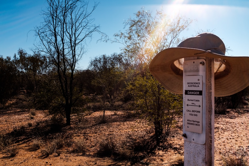 A wide-brimmed hat hangs on a warning sign in a desert area with trees.