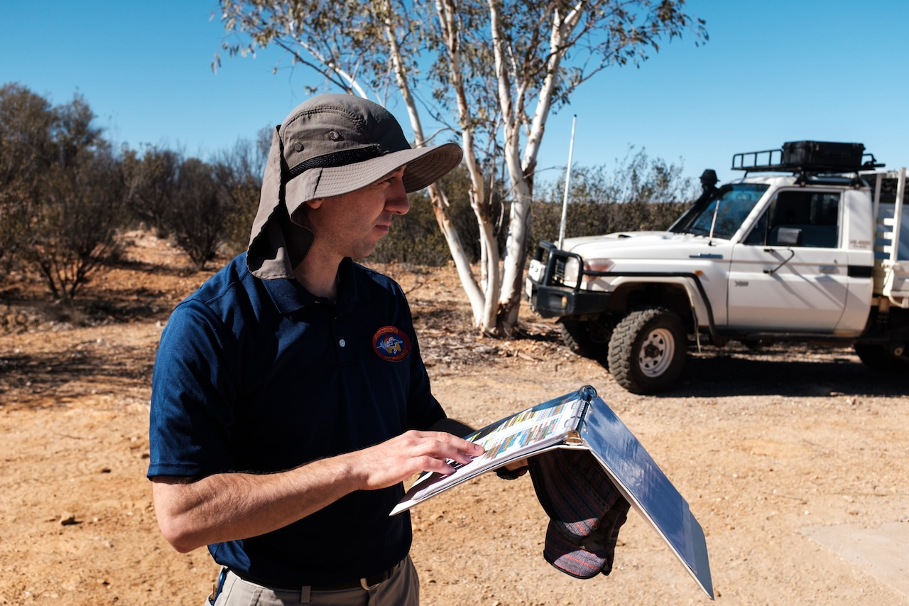 A man holds a binder in the desert near a tree and a truck.