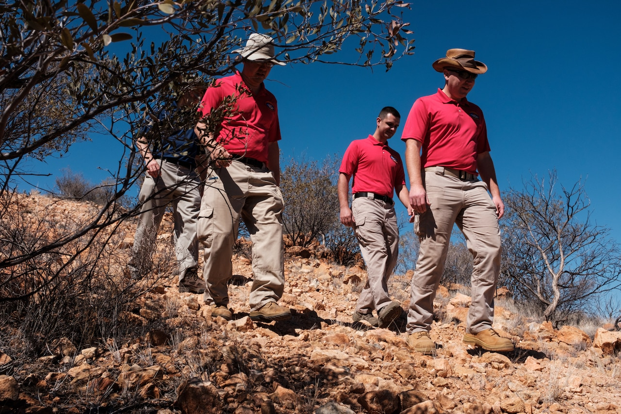 Four men in khakis and polo shirts walk down a rock-covered hill.