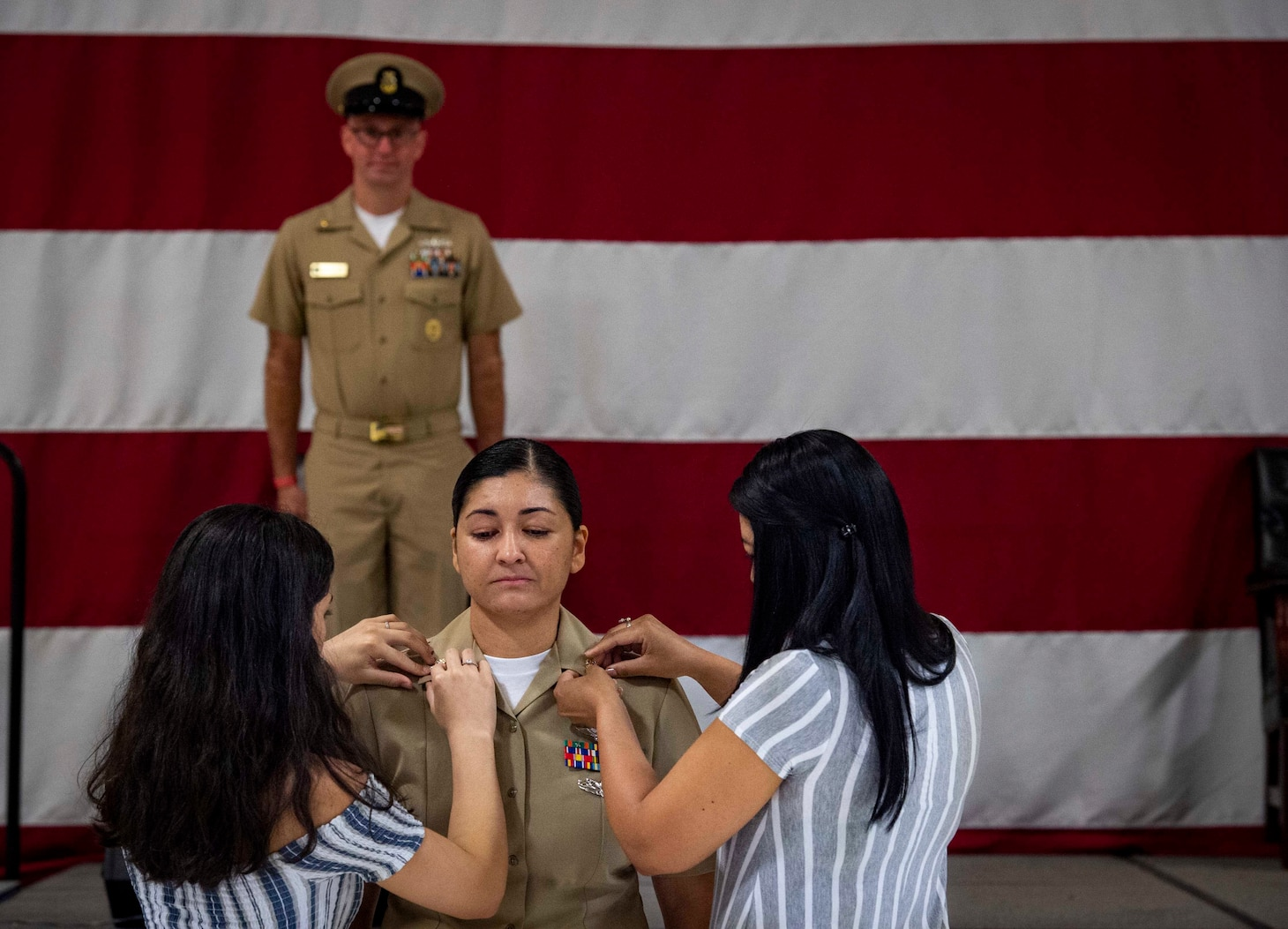 U.S. Fleet Forces Command (USFFC) 2019 Sea Sailor of the Year (SOY) Chief Aviation Structural Mechanic Carolina Berrio, of Strike Fighter Squadron (VFA) 81 and an Armenia, Columbia native, center, is pinned by her daughter and sister during a chief pinning ceremony at the Center for Naval Aviation Technical Training hangar onboard Naval Air Station Oceana, June 2, 2020.
