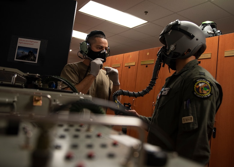An Airman talks into a headset while another Airman wears a helmet and oxygen mask.