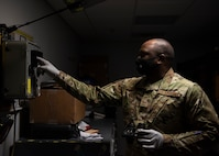An Airman holding a pair of night vision goggles touches a test station for night vision goggles.