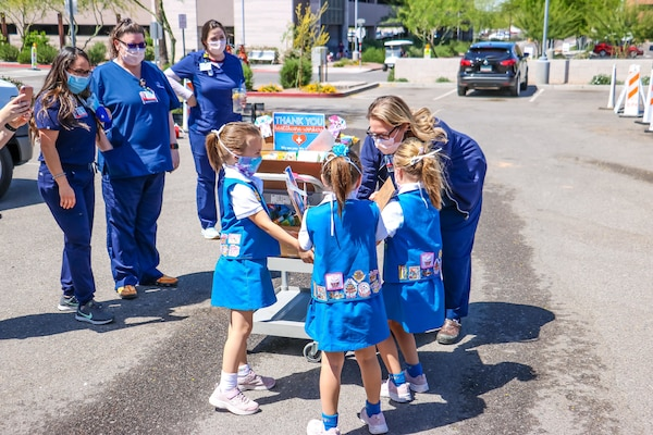 Nurses receive a package of treats from children in front of a hospital