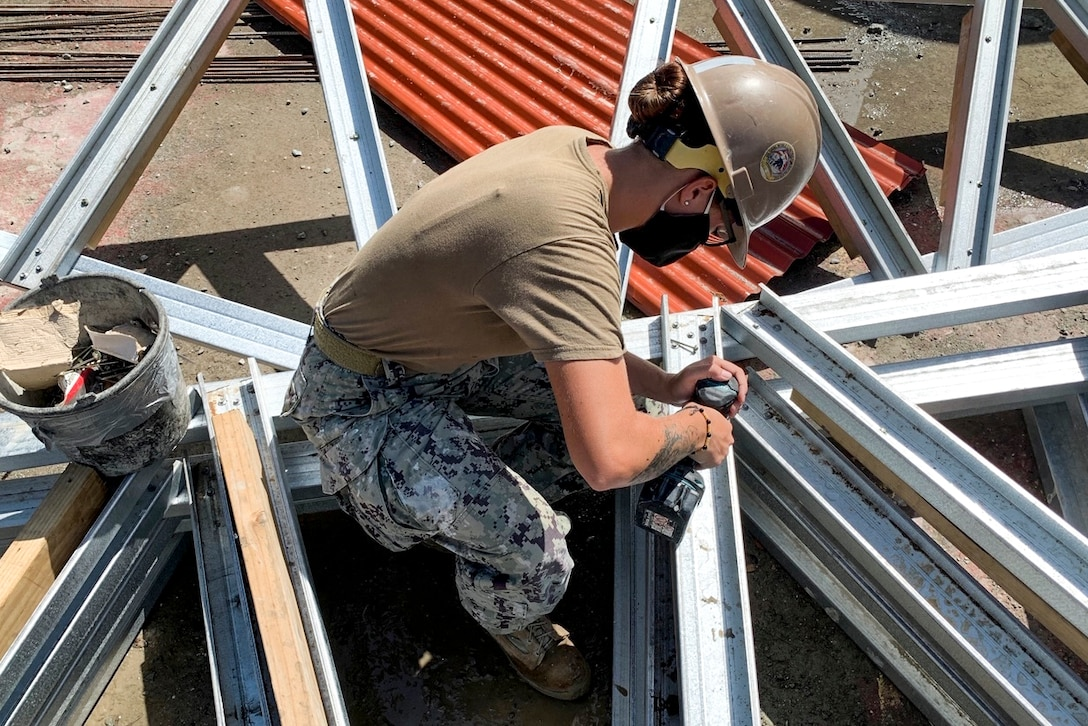 A sailor wearing a mask and hard hat sits and drills boards.