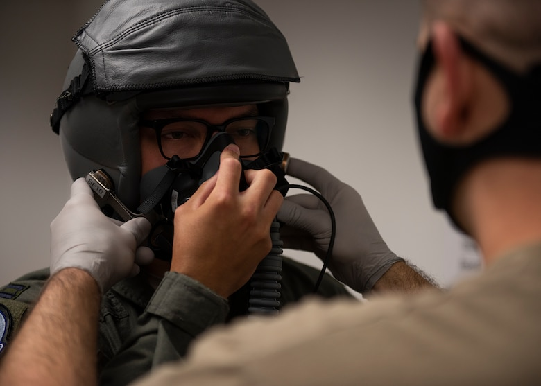An Airman wearing a helmet holds an oxygen mask to their face while another Airman secures the oxygen mask to the helmet.