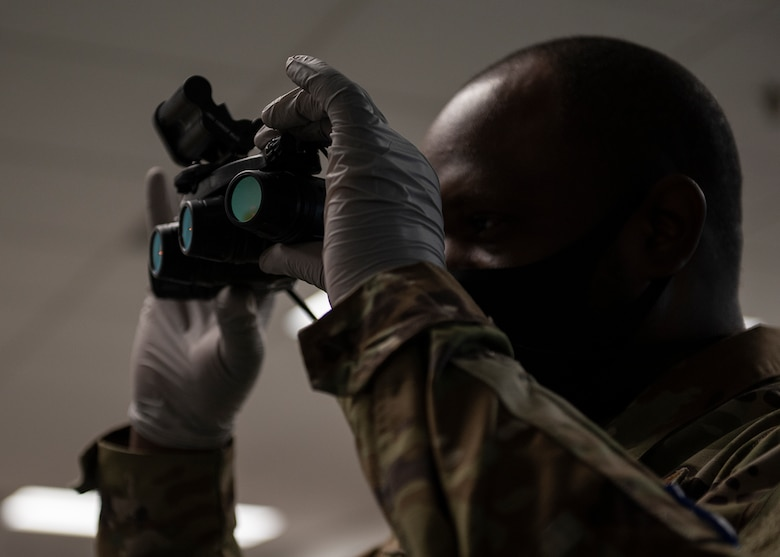 An airman looks through a pair of night vision goggles.