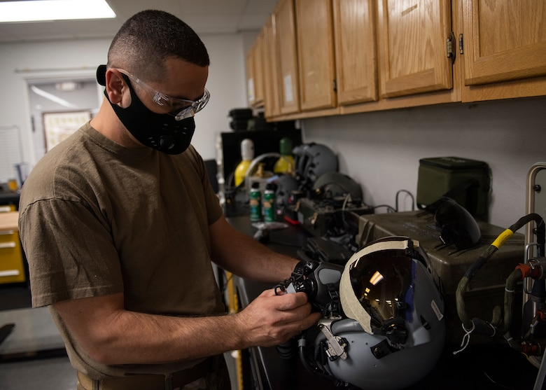 An Airman works on a fighter pilot helmet.