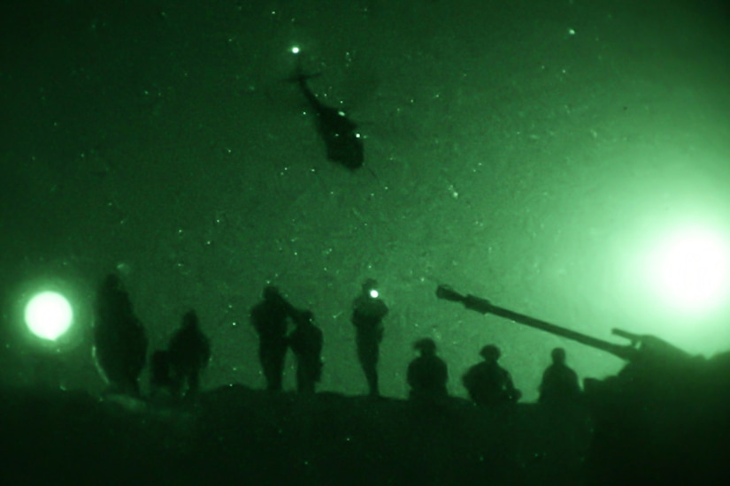 A helicopter flies over troops at night.