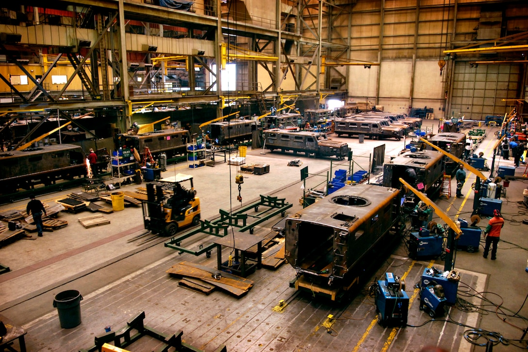 Inside a large manufacturing facility, multiple military vehicles are in various states of assembly.