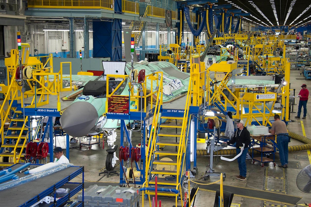 In a large, brightly-lit facility with blue and yellow scaffolding, military aircraft are lined up in varying states of assembly.