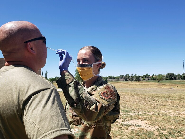 Airman 1st Class Sinead Brosnan, 27th Special Operations Medical Operations Squadron aerospace medical technician, takes a nasal swab of a deployer to test for COVID-19 before a deployment at Cannon Air Force Base, New Mexico, May 20, 2020. Over 100 nasal swabs were collected from deployers in order to meet theater requirements. (Courtesy Photo)