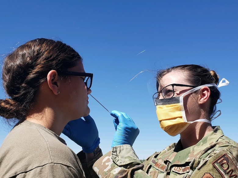 Staff Sgt. Ashley Malawey, 27th Special Operations Aerospace Medical Squadron aerospace medical technician, takes a nasal swab of a deployer to test for COVID-19 before a deployment at Cannon Air Force Base, New Mexico, May 20, 2020. After retrieving the nasal swabs, members of the 27th Special Operations Medical Group packaged and prepared the swabs for air transport to be delivered to Lackland Air Force Base, Texas. (Courtesy Photo)