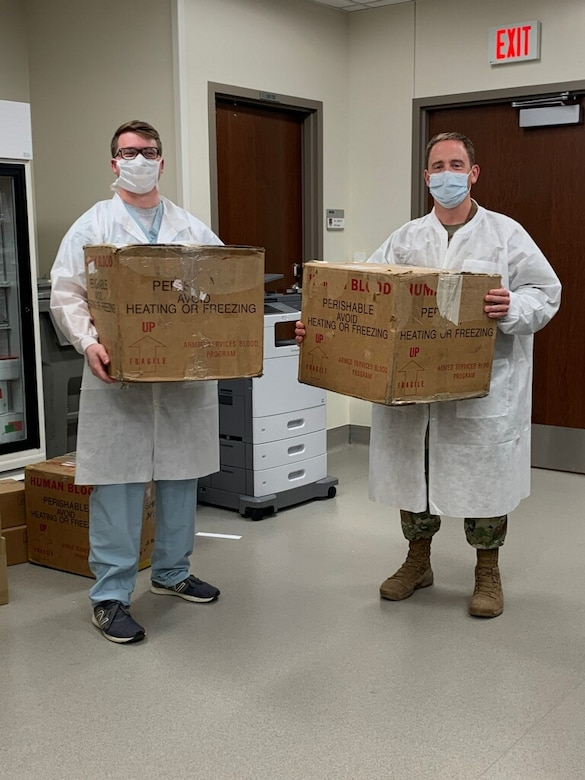 Lab assistants from Wilford Hall Medical Center at Lackland Air Force Base, Texas, hold up packages containing nasal swabs that are to be delivered to Brooke Army Medical Center to test for COVID-19, May 20, 2020. The swabs were collected, delivered, and tested in a 12-hour span. (Courtesy Photo)